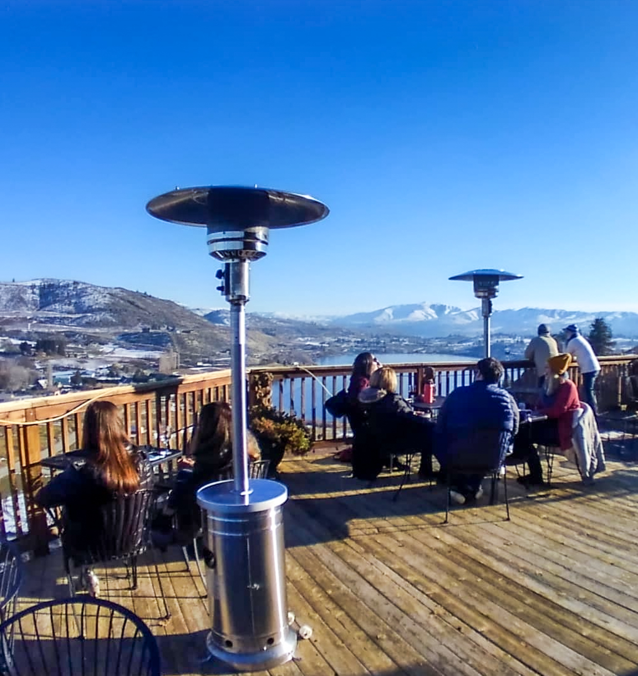 Deck with people at tables and heat lamps, overlooking a large lake. Snow-covered mountains are in the distance, with a bright blue winter sky.