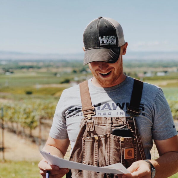 A man wearing overalls and a ballcap looks down at a paper in his hands as he speaks. Vineyards and a blue sky are behind him.