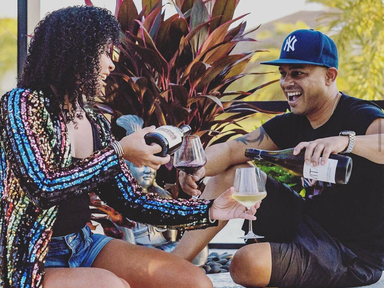 A woman wearing a colorful striped shirt and shorts and a man wearing a ballcap and shorts sit on the ground in front of a large potted plant. Each pours wine from a bottle into a glass  that the other is holding and they are smiling broadly.