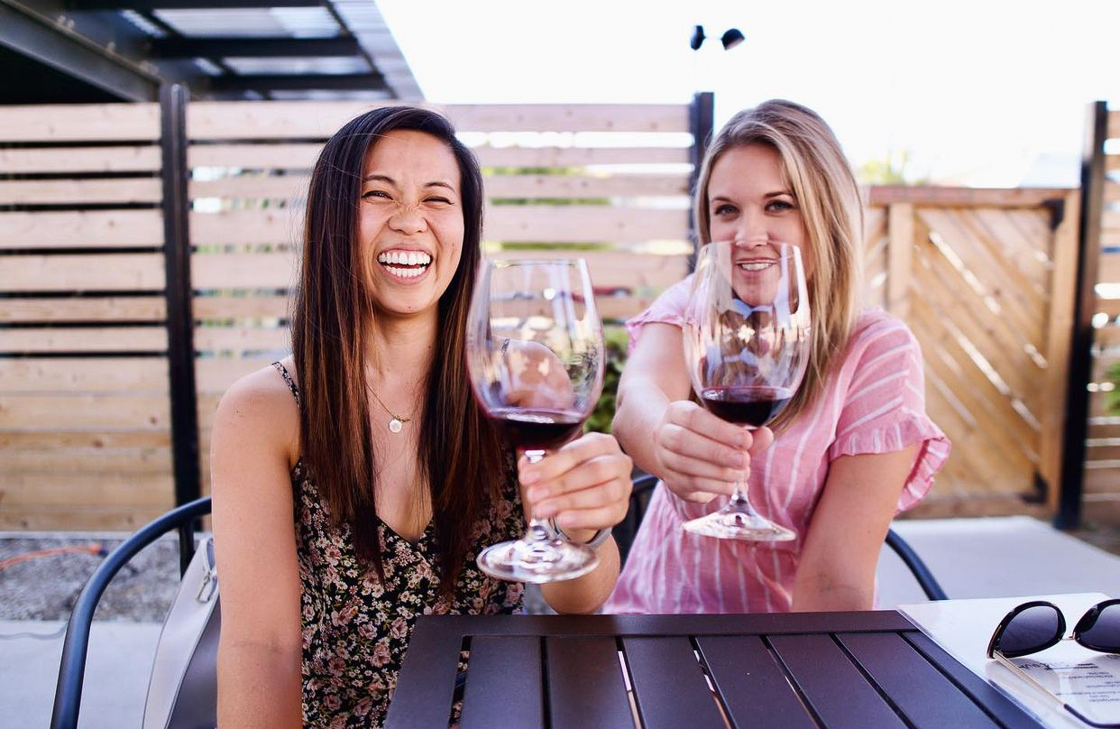 Two young woman smile and hold wine glasses with red wine up to the camera. The woman on the left has long, dark brown, straight hair in a black floral shirt and the other woman has medium length blonde hair in a striped pink shirt.