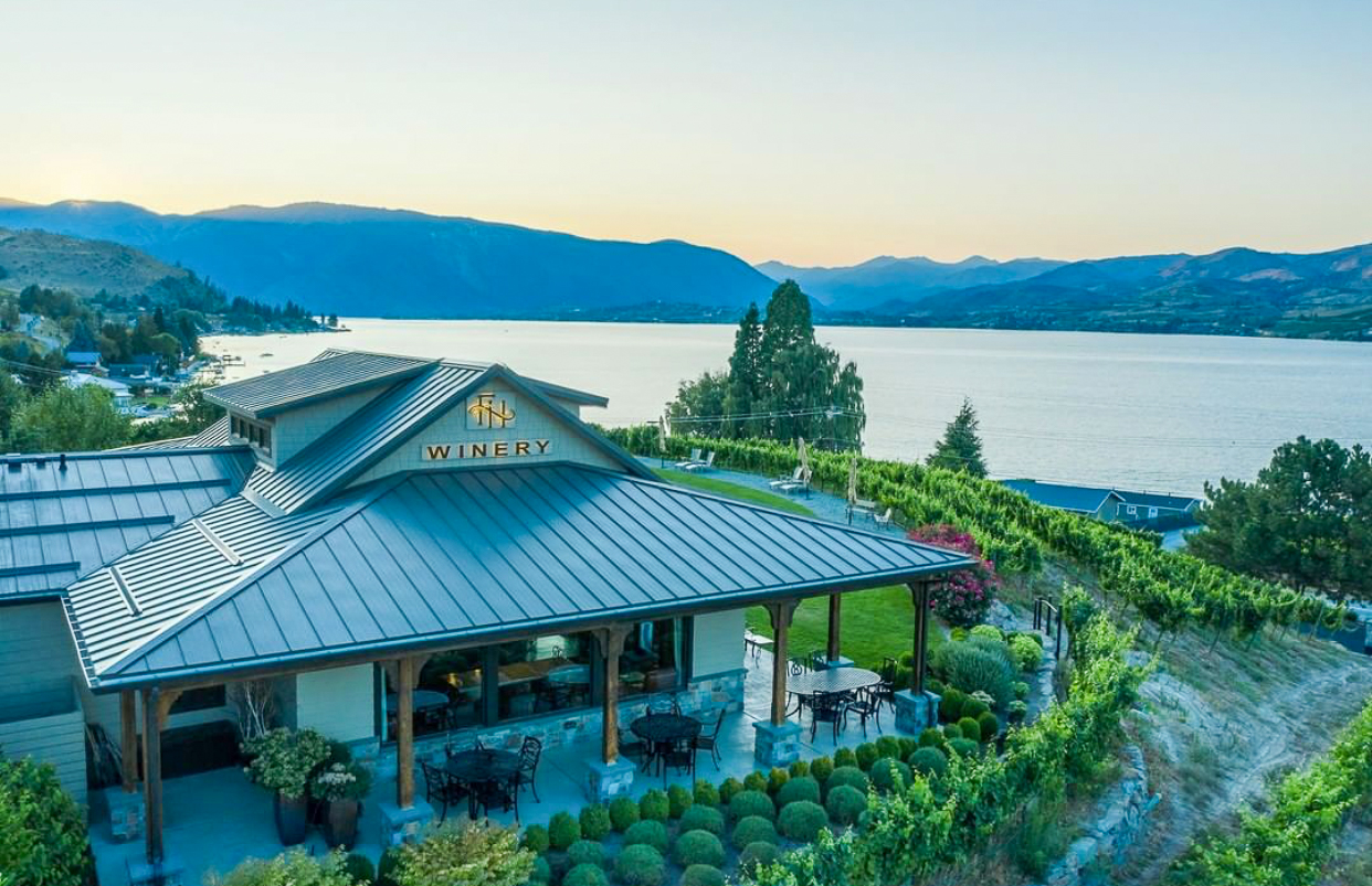 Building with overhanging roof and patio with tables and chairs in foreground surrounded by grape vines. A large lake and mountains are in the background, all in evening light.