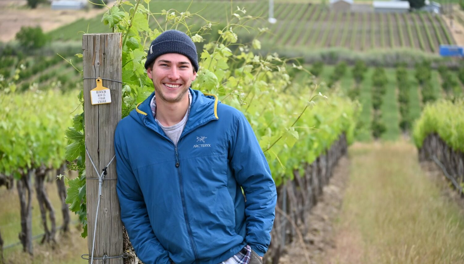 A young man in a beanie hat and blue jacket smiles and leans against a post with a vineyard to the left.