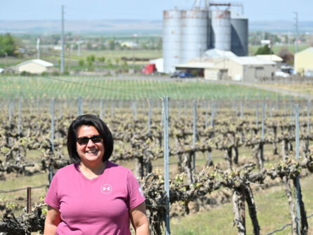 A woman in a pink shirt and sunglasses stands with short dark hair in front of vines without leaves, large cylindrical agricultural buildings are in the background