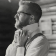 Black and white image of a profile view of a man with glasses and short hair buttoning the collar of his white shirt in front of a cabin wall.