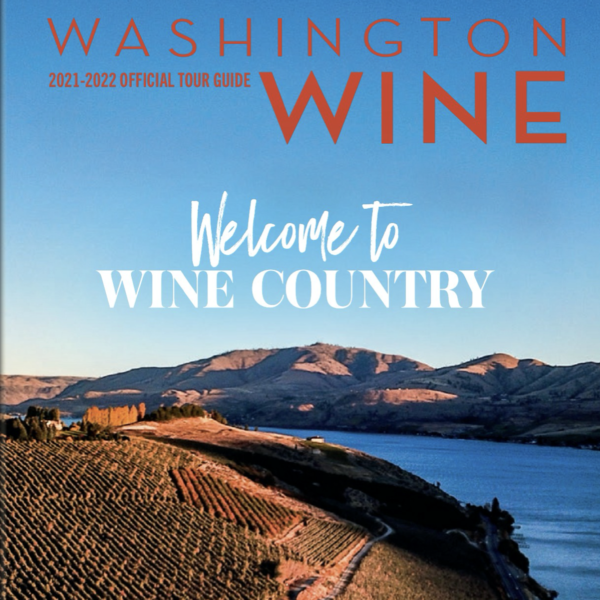 """Front cover of the WA wine tour guide, titled """"Washington Wine 2021-2022 Official Tour Guide"""" with """"Welcome to Wine Country"""" below the title. The image of a large river and vineyards on a hillside."""