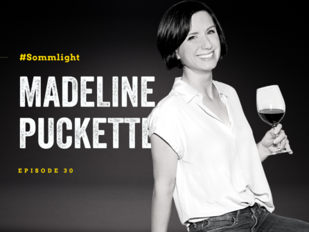"""black and white image of a woman (Madeline Puckette) with jaw-length dark hair smiling at the camera wearing a white blouse and holding a glass of red wine. Text overlay reads: """"Sommlight, Madeline Puckette, episode 30"""""""