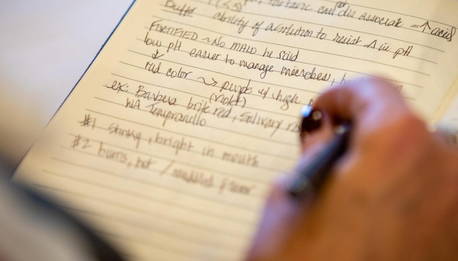 A hand holding a pen rests above a page with hand-written notes.