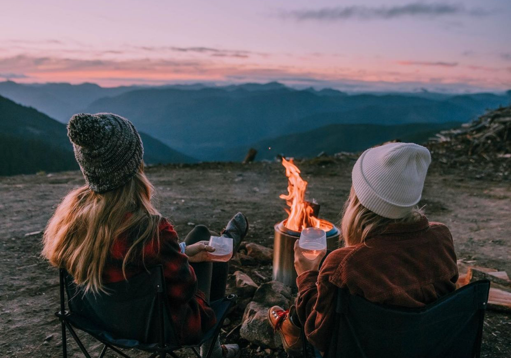 View from behind of two women in beanies and sweaters sitting by a campfire with glasses of wine. They look out toward the mountains in the distance and the sky is faded pink and purple.