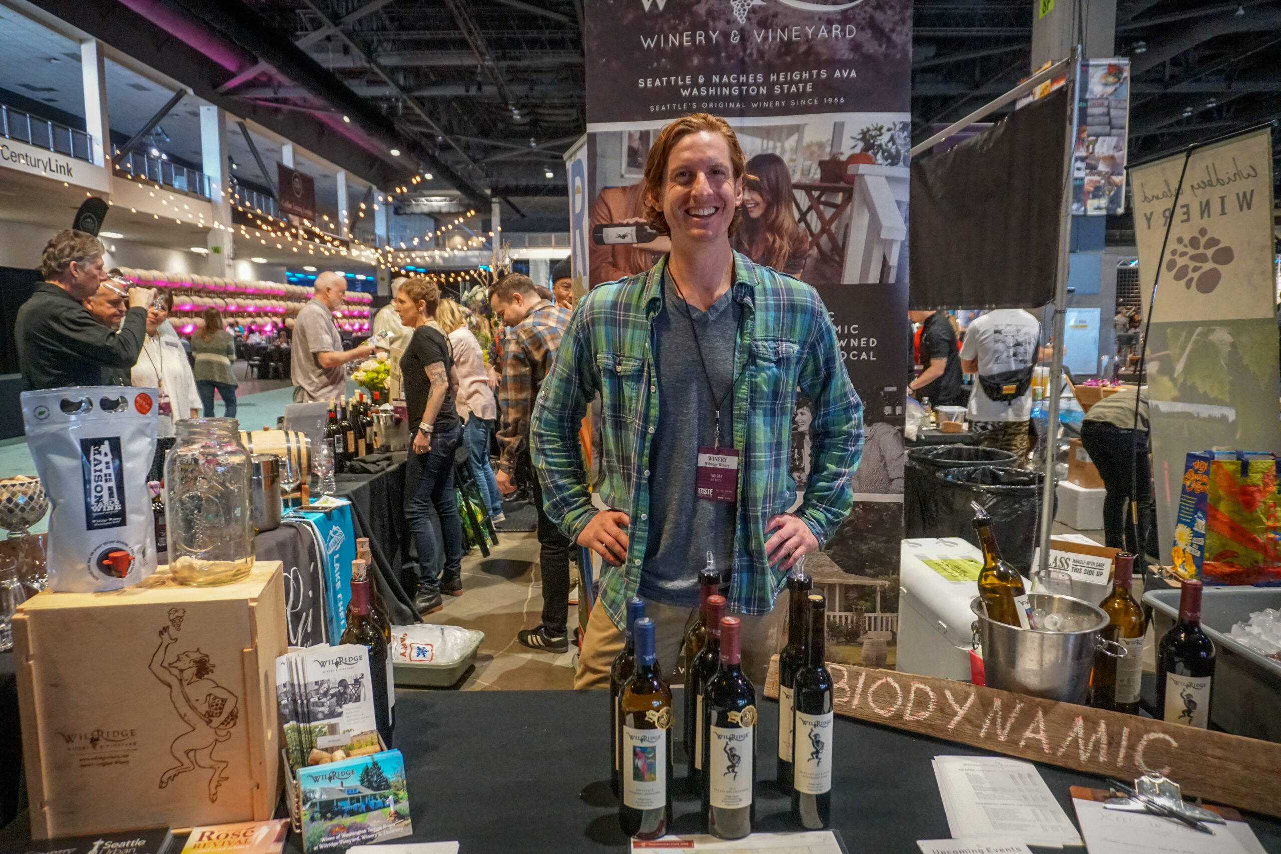 A man earing a blue and green plaid shirt smiles with his hands on his hips in front of a table with bottles of wine. People and more tables are in the background.