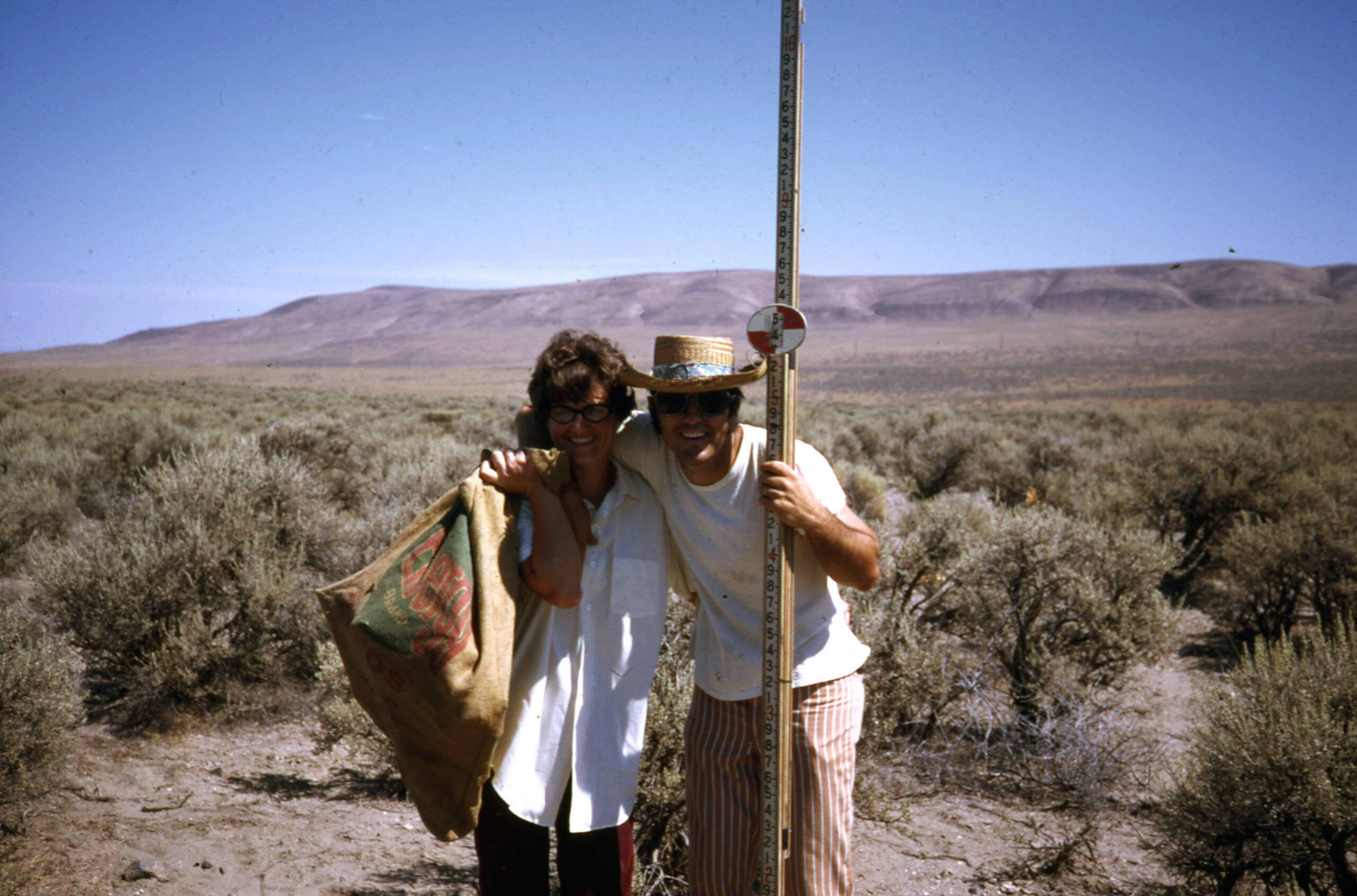 A man and a woman smile in a sagebrush field with rolling hills and blue sky behind. The woman holds a burlap sack over her shoulder and the man's arm is around her neck and holds a tall square measuring pole.