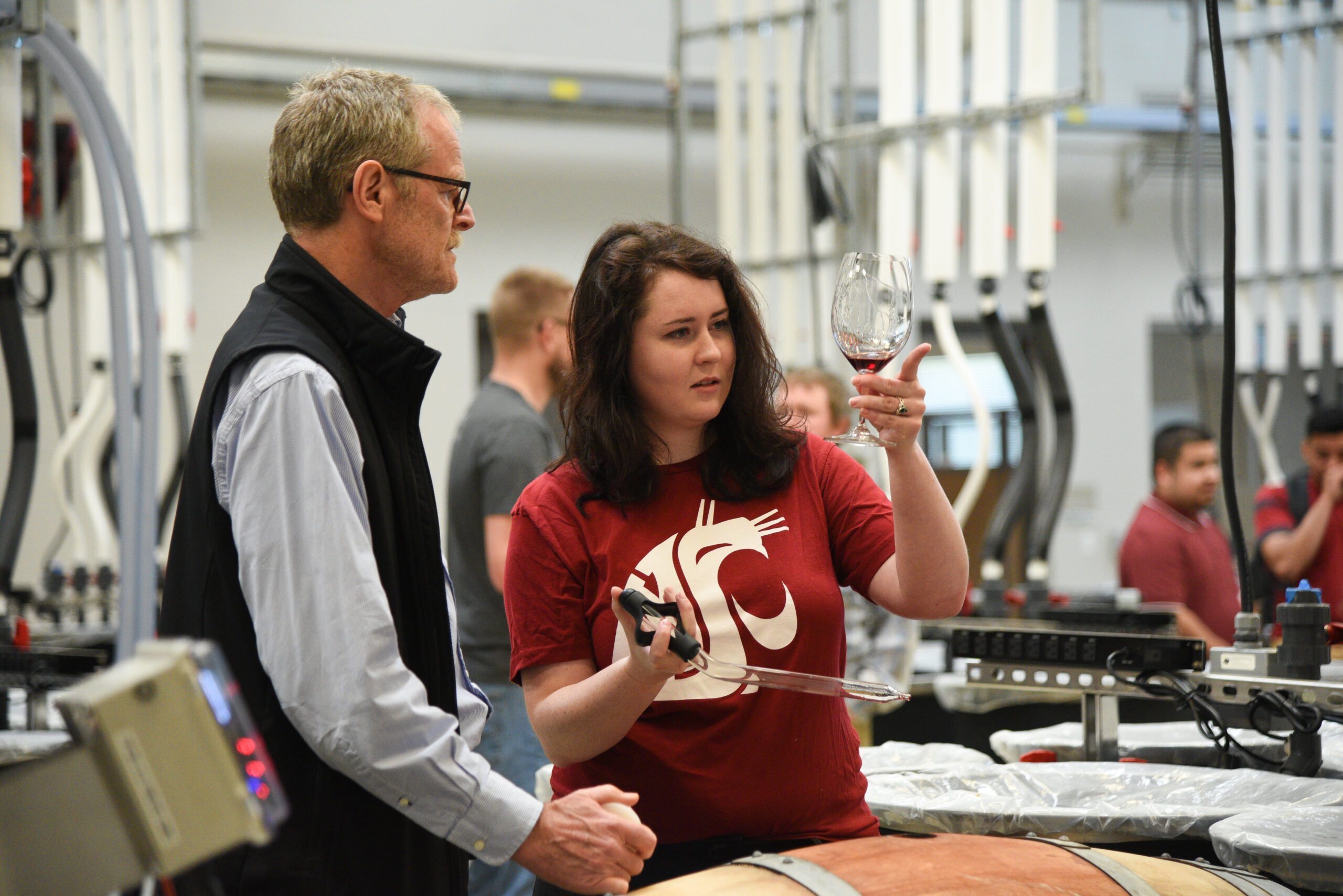 A young woman wearing a red WSU shirt holds a glass with red wine up to eye level and examines it. A man standing next to her wearing a black vest also looks at the glass. The background is a busy lab with tubes and other students.