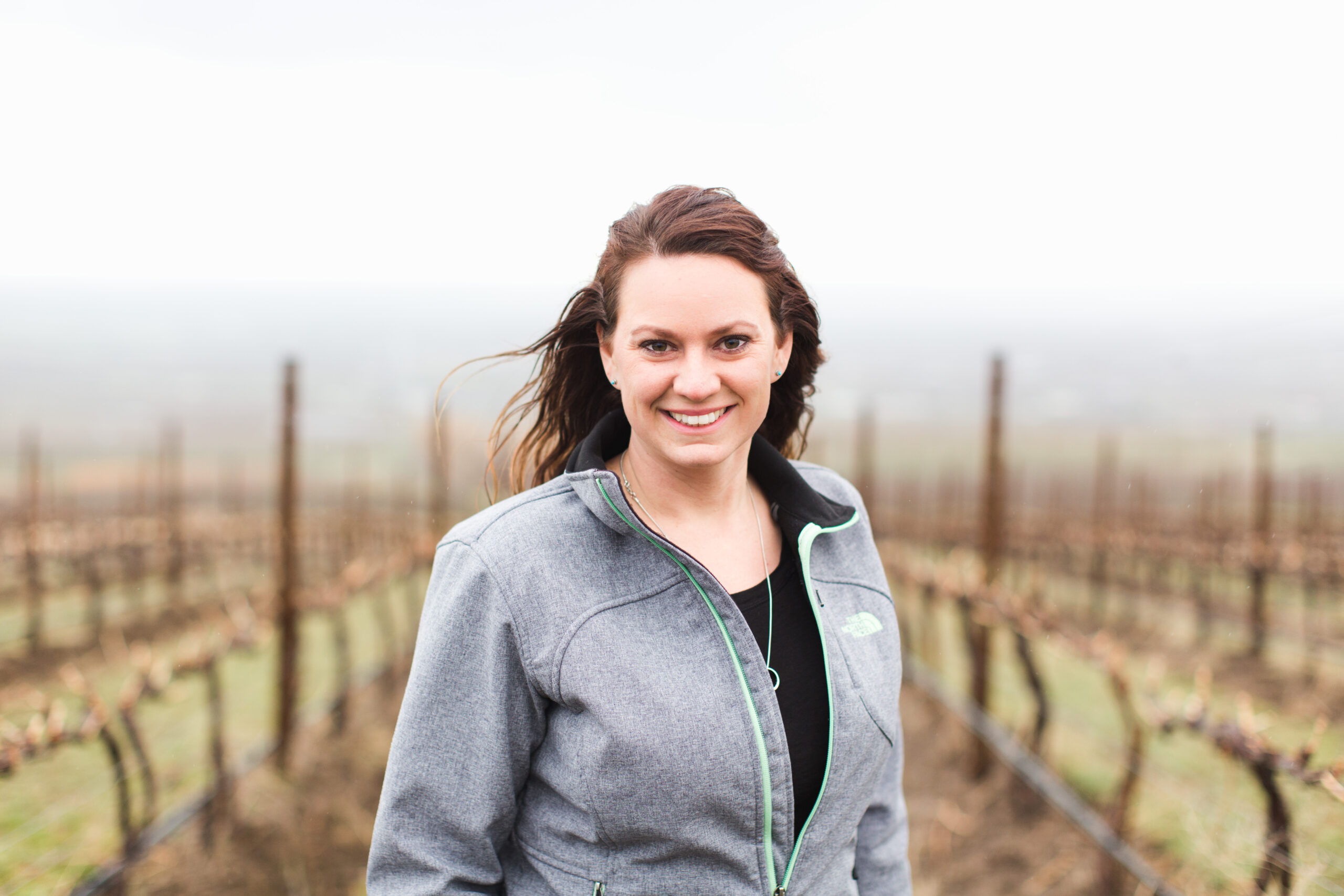 A woman with long dark hair and a grey jacket smiles and stand in front of grape vines without leaves, which are out of focus.
