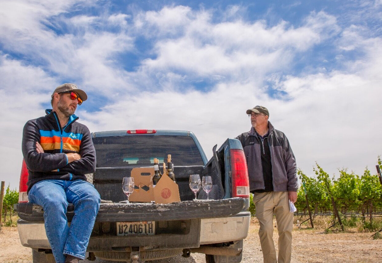 A man sits with arms folded on the tailgate of a truck while another man looks at him. Bottles of wine are on the truck bed between them and green vines are to their left, with a bright blue sky above.