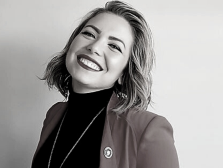 black and white image of a woman (Jennifer Estevez) with shoulder-length hair smiling at the camera, wearing a blazer and dark turtleneck