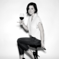 A black and white image of a woman (Madeline Puckette) with jaw-bone length dark hair sitting on a stool turning toward the camera. She holds a glass of red wine in her hand and smiles.