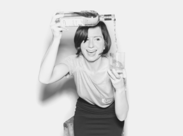 black and white image of woman with jaw-length dark hair pouring a liquid from a bottle into a glass in her other hand. She is bent forward and hold the bottle above her head.