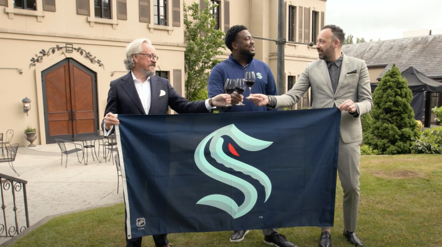 three men hold a flag with the S logo for the Seattle Kraken