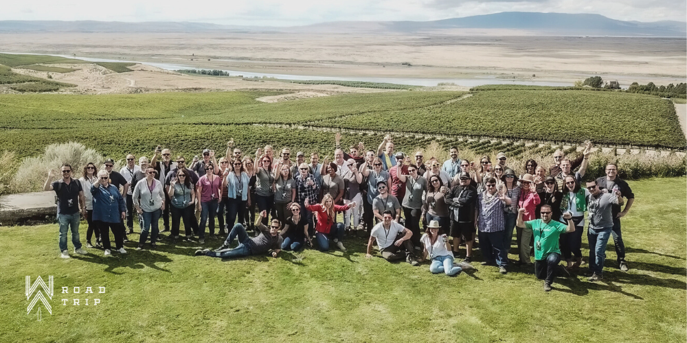 A large group of people stand in rows and look toward the camera and raise their hands. They stand on a green lawn with green vineyards and tan hills in the distance.