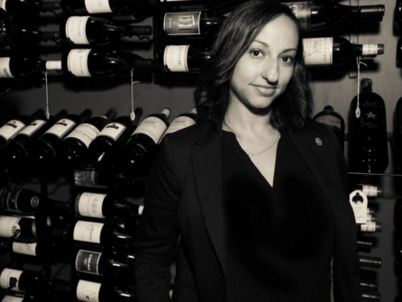 Cara De Lavallade standing in front of bottles.